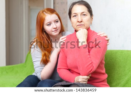 Teen girl asks for forgiveness from her mother. Focus on mature woman - stock photo