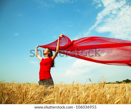 Teen girl at a wheat field with red fabric - stock photo