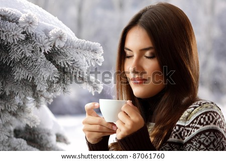 teen girl attractive drinking coffee over winter nature background - stock photo