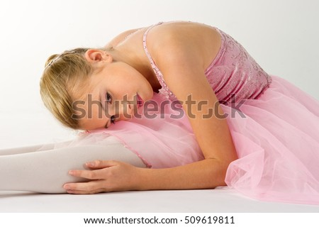 teen girl ballet dancer sitting in a tutu on a white background