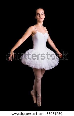 Teen girl ballet dancer standing in white tutu on black background - stock photo