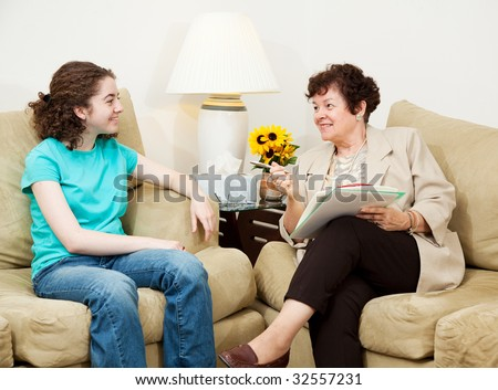 Teen girl being interviewed by a mature woman.  Could be college or job interview, or counseling session. - stock photo