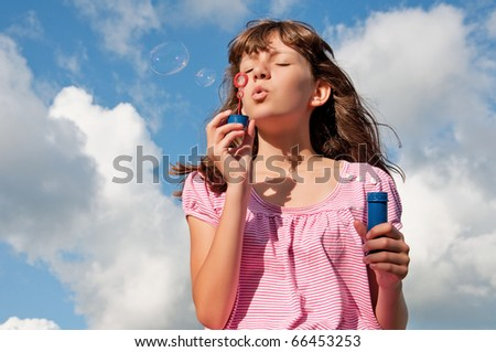 Teen girl blow bubbles, on background of the sky - stock photo