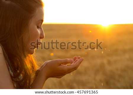 teen girl blowing at her palms filled with wheat grains standing at wheat field at sunset time - stock photo