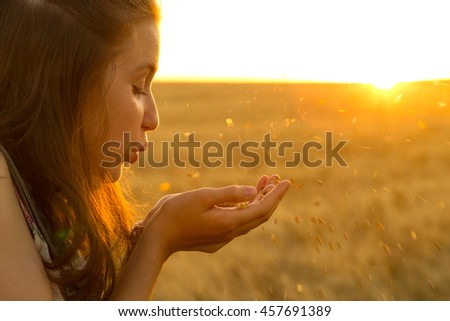 teen girl blowing at her palms filled with wheat grains standing at wheat field at sunset time