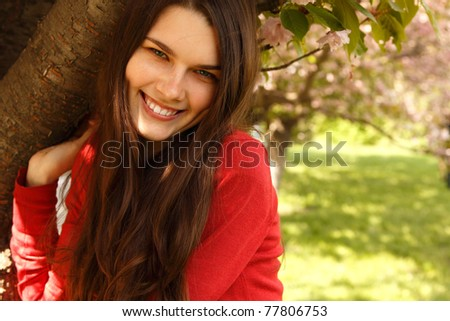 teen girl charming happy smiling in nature garden Japanese cherry tree - stock photo