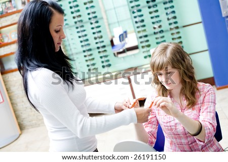 Teen girl choose an glasses in a shop - stock photo