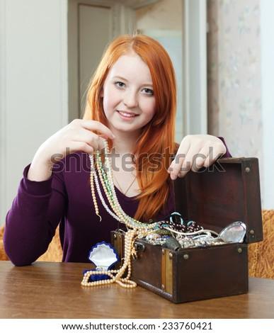 teen girl chooses jewelry in treasure chest  - stock photo