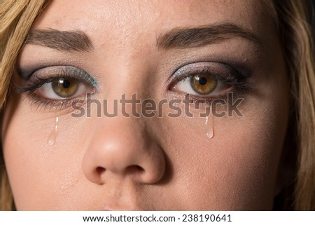 Teen girl crying, with a tear drop running down her cheek.