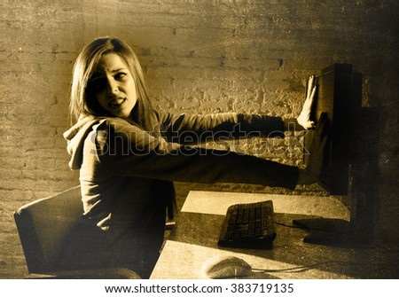 teen girl cyber abused suffering internet cyberbullying scared and desperate in fear face expression sitting in front of computer monitor in  bullying social problem edgy grunge lighting - stock photo