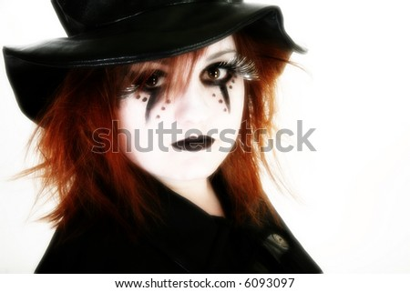 Teen girl dressed in Halloween make-up, black hat and cape over white.