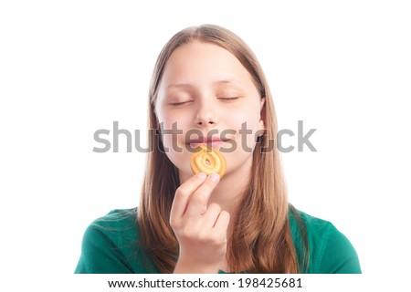 Teen girl eating cookie, studio shot - stock photo