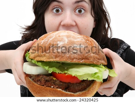 Teen girl eating huge giant hamburger with funny expression. - stock photo