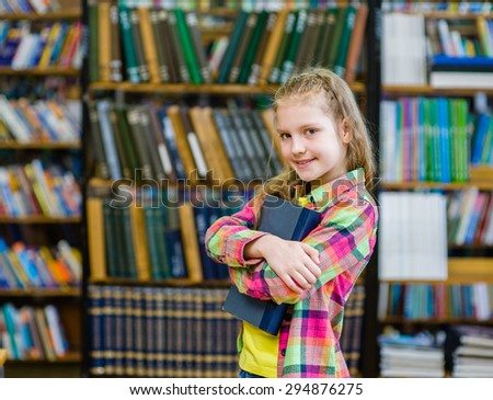 Teen girl embracing book in the library - stock photo