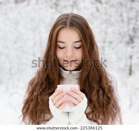teen girl enjoying big mug of hot drink during cold day - stock photo