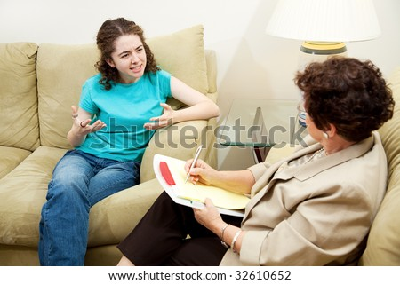 Teen girl expressing frustration in a session with her therapist. - stock photo