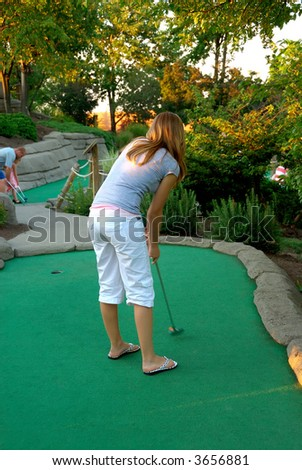 Teen girl golfing at a miniature golf place in summertime.