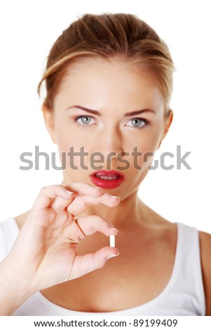 Teen girl holding a capsule pill