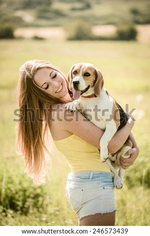 Teen girl holding her pet (beagle dog) - outdoor in nature - stock photo