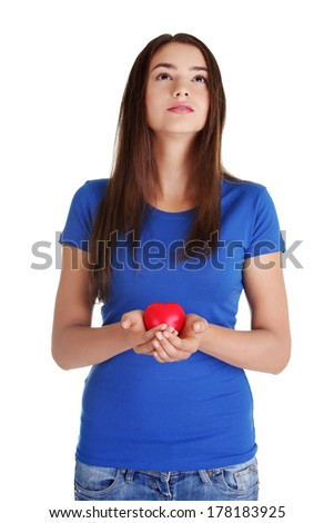 Teen girl holding red heart and looking up