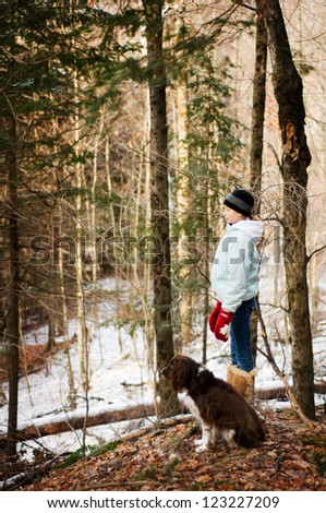 teen girl in a forest with her dog - stock photo