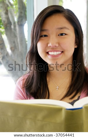 Teen girl in classroom smiling while reading a book