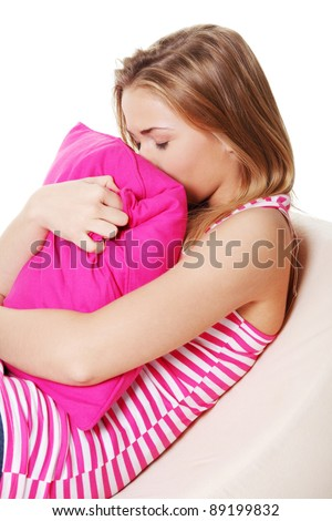 Teen girl in depression hugging pink pillow