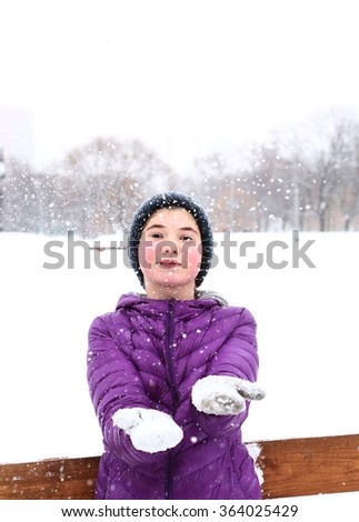 teen girl in down jacket and knitted woolen hat throw snow close up portrait on snowy white park background - stock photo