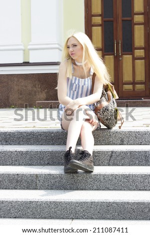 teen girl in gym shoes and a backpack sitting on the stairs - stock photo