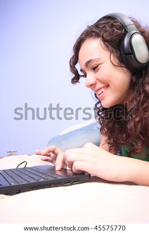 Teen girl in her bed looking on her laptop - stock photo
