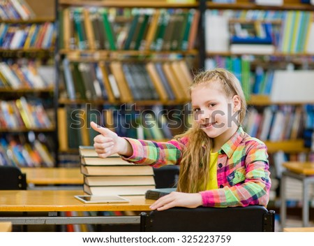 teen girl in library showing thumb up - stock photo