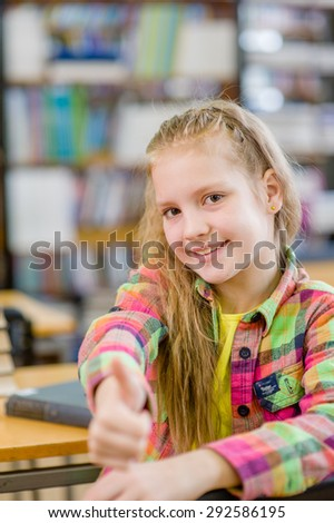 teen girl in library showing thumbs up - stock photo