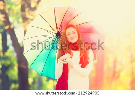 Teen girl in red scarf with umbrella at autumn outdoor - stock photo
