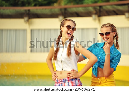 Teen girl in sunglasses laugh near the fountain in summer park. Girls dressed in shorts and a shirt. On summer vacation. The concept of true friendship. - stock photo