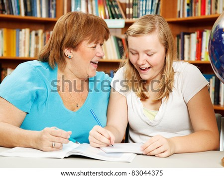 Teen girl in the library studying with her mother (or teacher.)