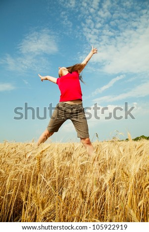 Teen girl jumping at a wheat field in a sunny day - stock photo