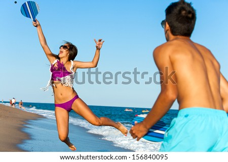 Teen girl jumping at beach tennis ball. - stock photo