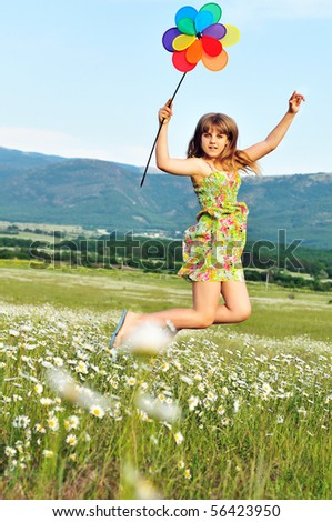 teen girl jumping in field and holding windmill