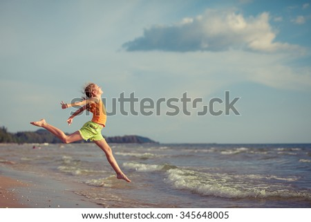 Teen  girl  jumping on the beach at the day time. Concept of happy youth. - stock photo