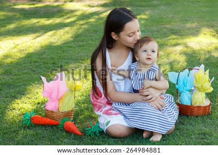 Teen girl kissing happy baby sister on green grass in park with wicker basket with chocolate eggs for Easter holiday. Selective focus