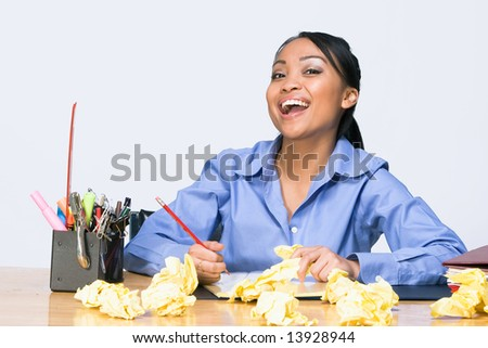 Teen girl laughs as she sits at a desk surrounded by crumpled paper, pens, pencils, and folders. Horizontally framed photograph - stock photo