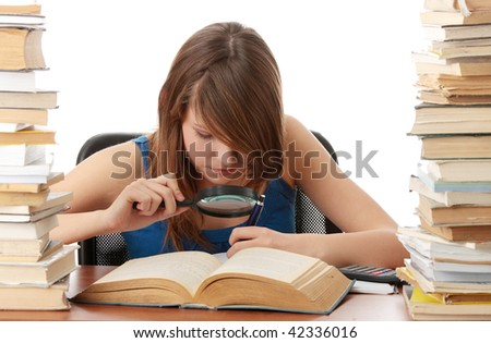 Teen girl learning at the desk with lot of books, isolated on white