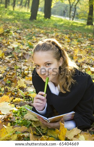 Teen girl lies in gold autumn park with her diary
