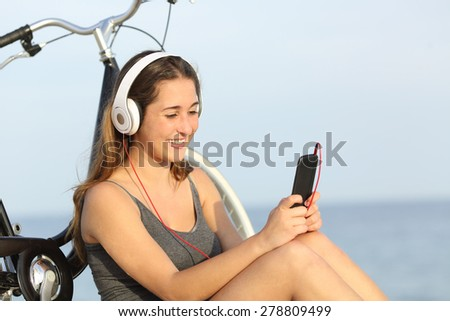 Teen girl listening music from a smart phone sitting with a bike on the beach - stock photo