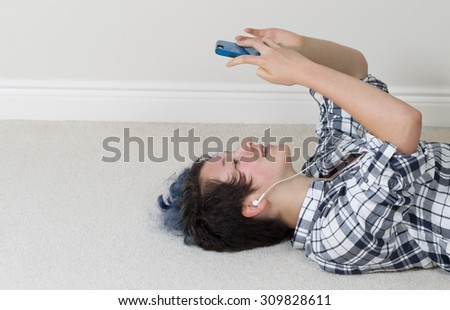 Teen girl looking at cell phone while lying on her back listening to music at home.  - stock photo