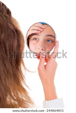 Teen girl looking at her pimples in the mirror - stock photo
