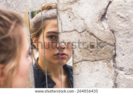 Teen girl looking at her reflection in the mirror fragments on the wall at street.  - stock photo