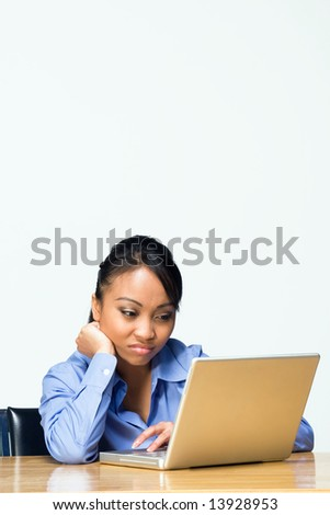 Teen girl looking bored types on a laptop computer as she sits at a desk. Horizontally framed photograph - stock photo