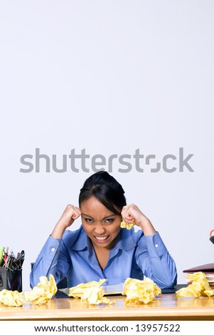 Teen girl looking frustrated as she sits at a desk surrounded by crumpled paper, pens, pencils, and folders. Vertically framed photograph - stock photo