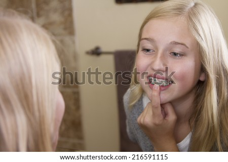 Teen girl looking in the mirror, examining her braces - stock photo